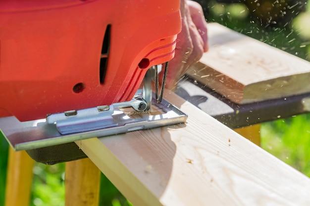 Ouvrier en bois couper un panneau en bois avec une scie sauteuse à l'extérieur, vue rapprochée d'un homme travaillant avec une scie sauteuse électrique et une planche en bois Photo Premium