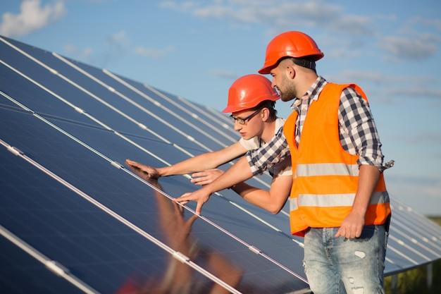 Ouvrier et contremaître maintenant panneau d'énergie solaire. Photo Premium