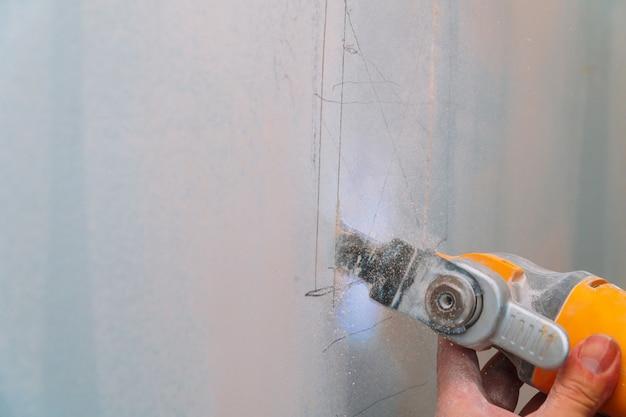 Ouvrier du bâtiment coupant des plaques de plâtre à l'aide d'une meuleuse d'angle électrique Photo Premium