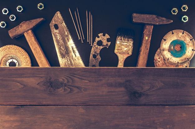 Ouvrier du bâtiment outils constructeur marteau, scie, clous, tournevis sur un fond en bois Photo Premium