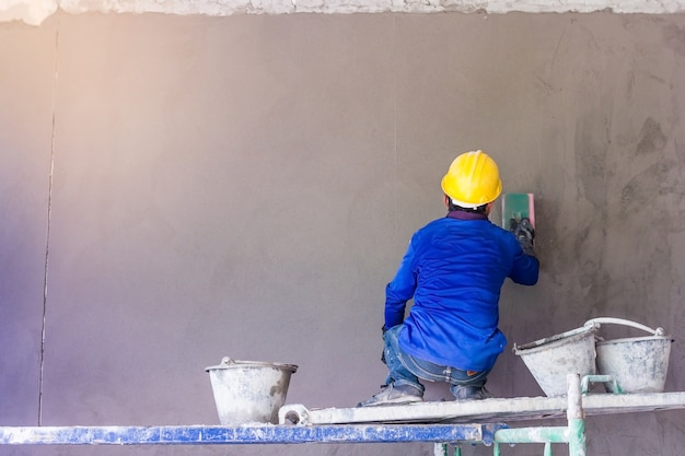 Ouvrier du bâtiment utilisant une truelle pour enduire le béton pendant les travaux de revêtement mural Photo Premium