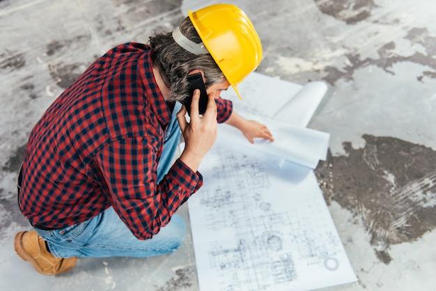 Ouvrier du bâtiment vérifiant les empreintes et parlant au téléphone Photo Premium