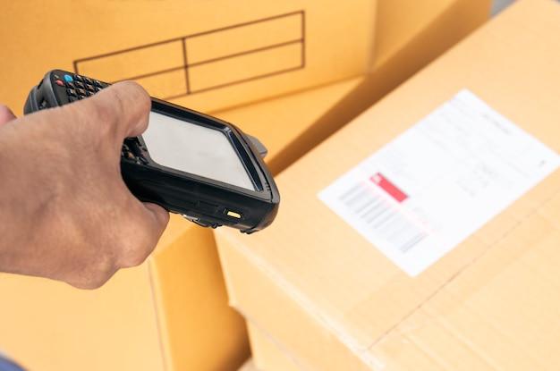 Ouvrier d'entrepôt est en train de scanner un scanner de code à barres avec l'étiquette du produit. Photo Premium