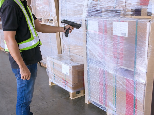 Ouvrier d'entrepôt tient un lecteur de code à barres avec balayage sur la palette d'expédition du produit Photo Premium