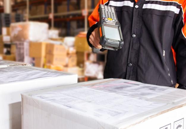 Un ouvrier d'entrepôt tient un lecteur de code à barres avec un laser à balayage sur une boîte à colis distribuée dans un entrepôt. Photo Premium