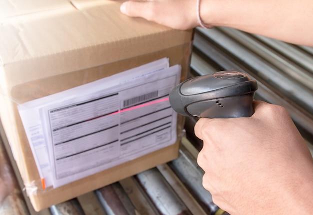 Ouvrier d'entrepôt tient un lecteur de code à barres avec numérisation sur le produit. Photo Premium