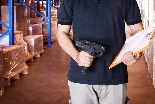 Un ouvrier d'entrepôt tient un lecteur de code à barres et un presse-papiers avec inventaire en magasin. Photo Premium
