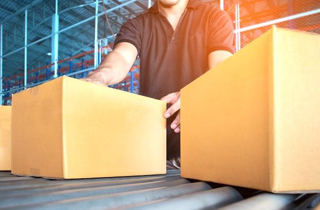 Ouvrier d'entrepôt travaille au tri d'un colis sur une bande transporteuse. Photo Premium