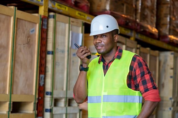 Ouvrier D'entrepôt Utilisant Un Récepteur Radio Portable Pour La Communication Dans Un Grand Entrepôt. Photo Premium
