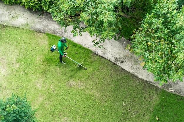 Ouvrier homme couper l'herbe avec une tondeuse à gazon Photo Premium