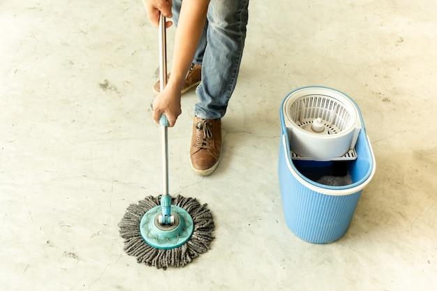 Ouvrier homme avec vadrouille nettoyage de sol dans le café. Photo Premium