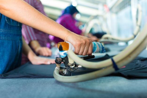 Ouvrier indonésien avec fer plat dans une usine textile Photo Premium