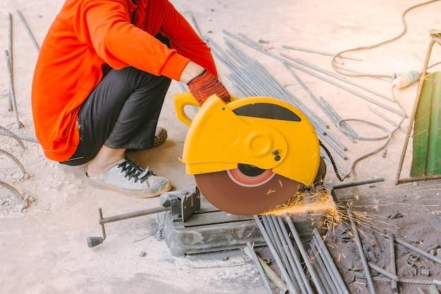 Ouvrier industriel coupant des tiges de renforcement en métal avec beaucoup d'étincelles tranchantes Photo Premium