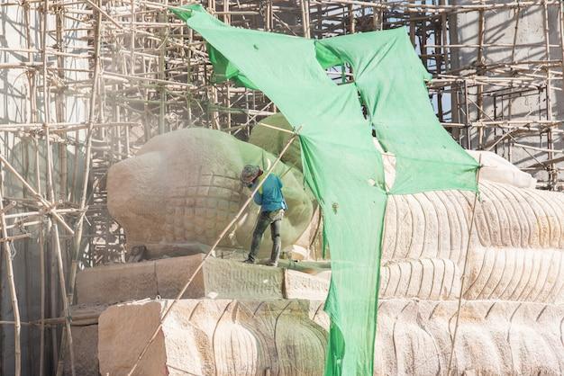 Ouvrier industriel utilisant une meuleuse d'angle professionnelle pour tailler la pierre de bouddha. Photo Premium