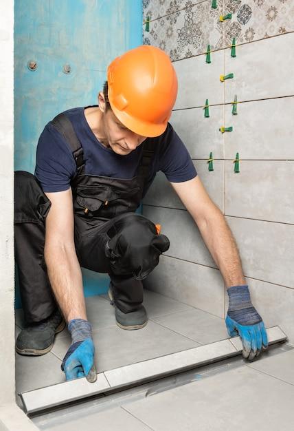 Ouvrier Installant Un Couvercle De Drain Décoré De Carreaux De Céramique Dans La Salle De Bain Photo Premium