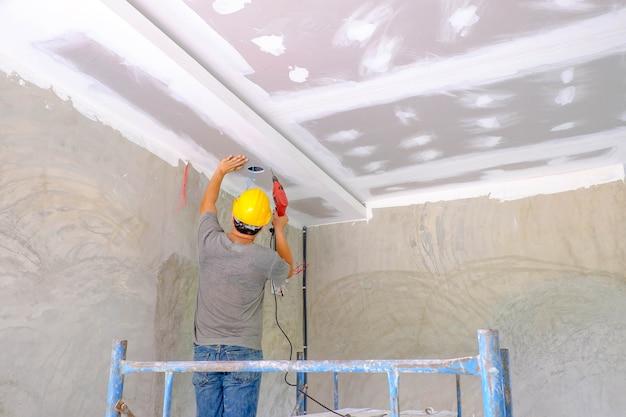 Ouvrier installant le plafond de panneau Photo Premium