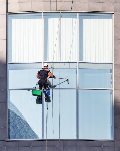 Ouvrier nettoyant les vitres et les immeubles de bureaux Photo Premium