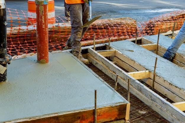 Ouvrier nivelant la chaussée en béton. coulée de béton Photo Premium