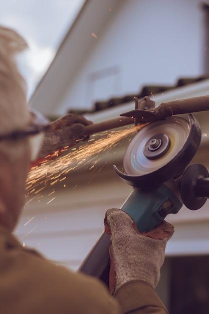 Ouvrier / ouvrière de meuleuse coupe le métal Photo Premium