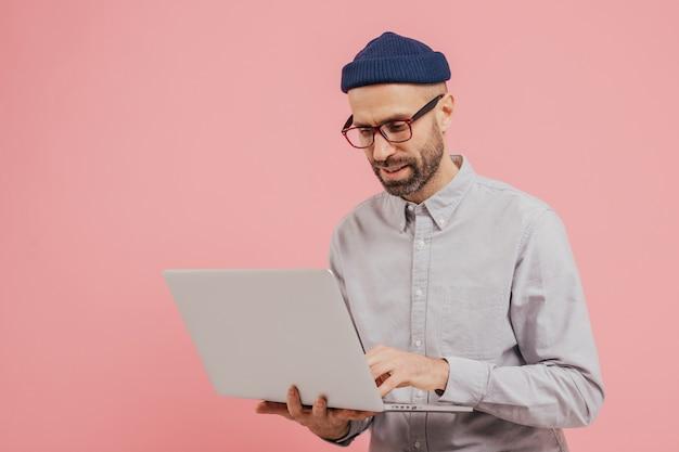 Un ouvrier professionnel cherche un film intéressant à regarder, utilise un gadget, saisit des informations sur un ordinateur portable Photo Premium