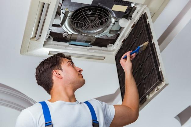 Ouvrier réparant une unité de climatisation au plafond Photo Premium