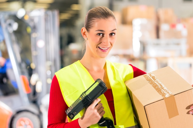 Un ouvrier scanne un colis dans un entrepôt d'expédition Photo Premium