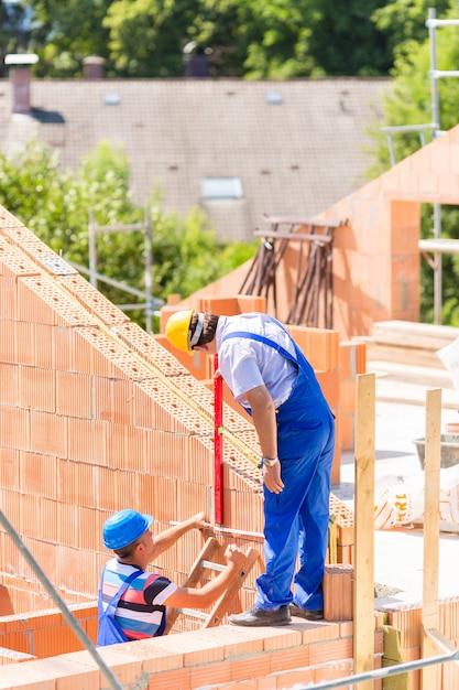 Ouvrier vérifiant les murs sur le chantier de construction Photo Premium
