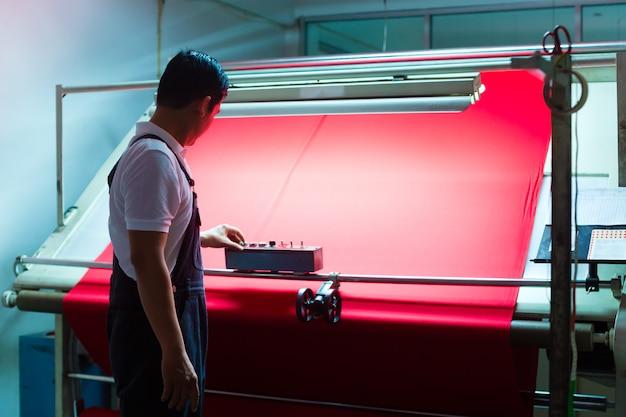 Une ouvrière asiatique contrôle des tissus dans une usine textile Photo Premium