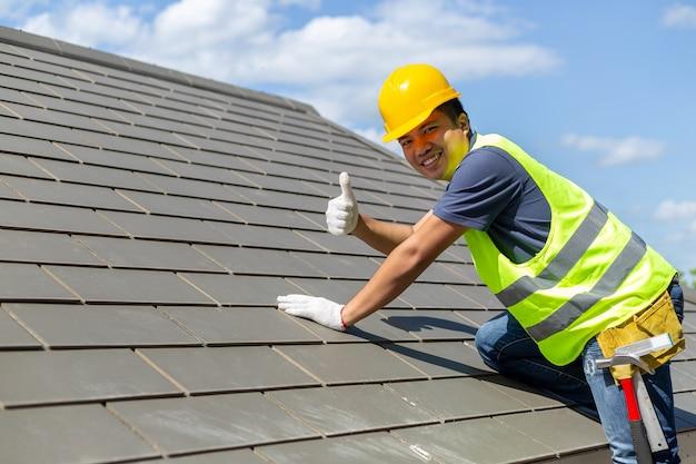 Les ouvriers asiatiques de couverture de tuiles ont levé les pouces pour indiquer la stabilité du toit. Photo Premium