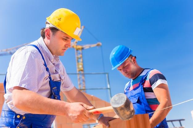 Ouvriers de chantier de construction de murs sur la maison Photo Premium