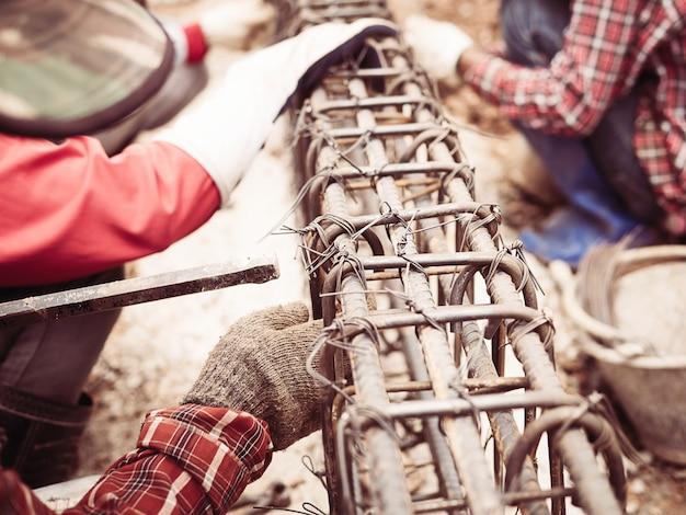 Les ouvriers du bâtiment installent des tiges d'acier dans une poutre en béton armé Photo gratuit