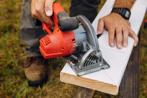 Ouvriers utilisant des scies à chaîne, des poutres en bois Photo Premium