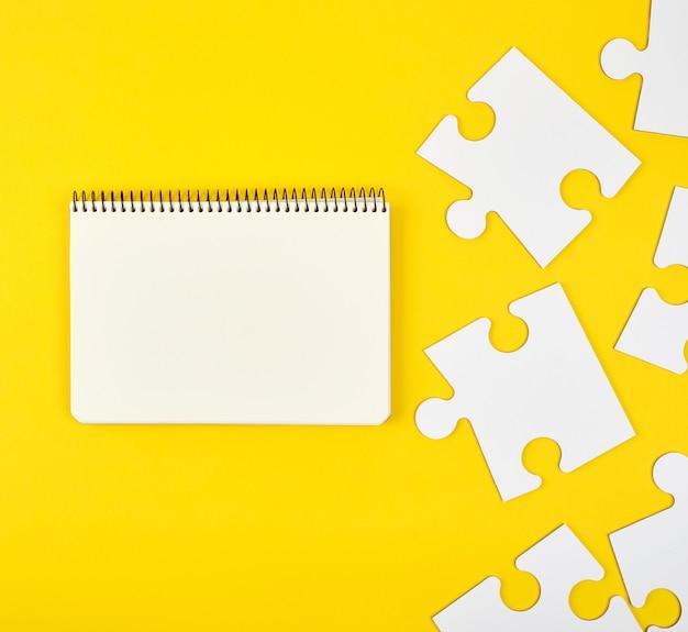 Ouvrir un cahier sur un fond jaune, à côté de grands puzzles vierges Photo Premium