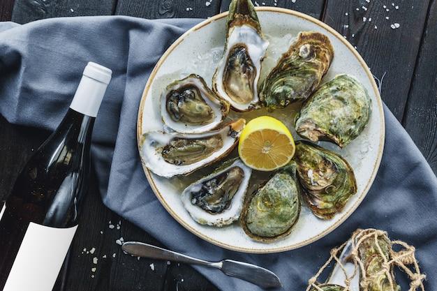 Ouvrir les huîtres humides sur une assiette avec du citron Photo Premium