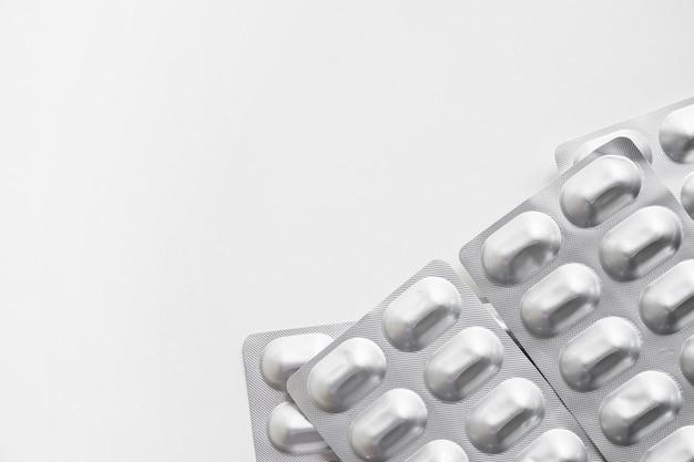 Packs de médicaments en argent réalistes sur fond blanc Photo gratuit