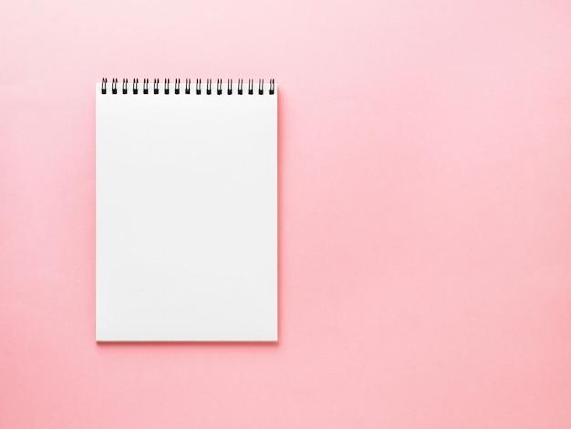 Page blanche de bloc-notes vide sur le bureau rose, couleur de fond. vue de dessus, vide pour le texte. Photo Premium