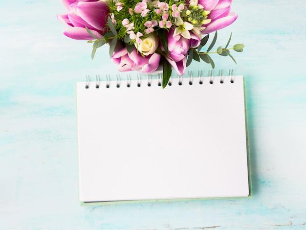 Page blanche de cahier vierge avec des fleurs roses pourpres. fond de fond Photo Premium
