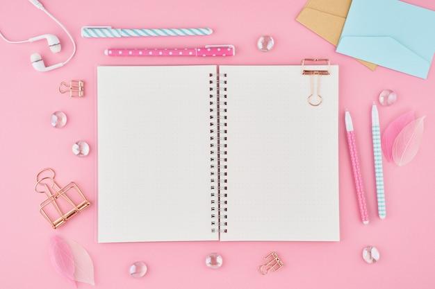 Page de bloc-notes vierge dans le journal de balle sur le bureau rose vif. vue de dessus de la table lumineuse moderne Photo Premium