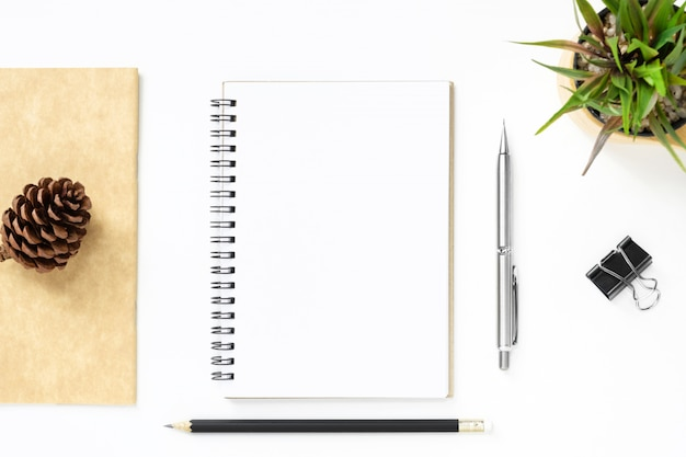Page de cahier vierge au-dessus d'une table de bureau blanche avec un stylo Photo Premium