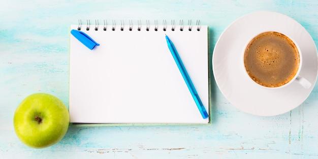 Page de cahier vierge avec stylo bleu et tasse de fleurs de café Photo Premium