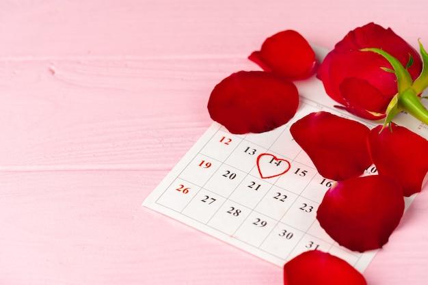 Page De Calendrier De Février Avec Rose Rouge Sur Table En Bois Rose Se Bouchent Photo Premium
