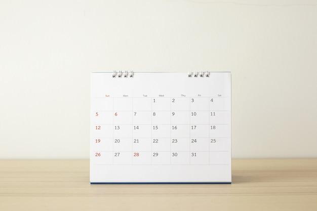 Page De Calendrier Gros Plan Sur Table En Bois Avec Fond De Mur Blanc Concept De Réunion De Planification D'entreprise Photo Premium
