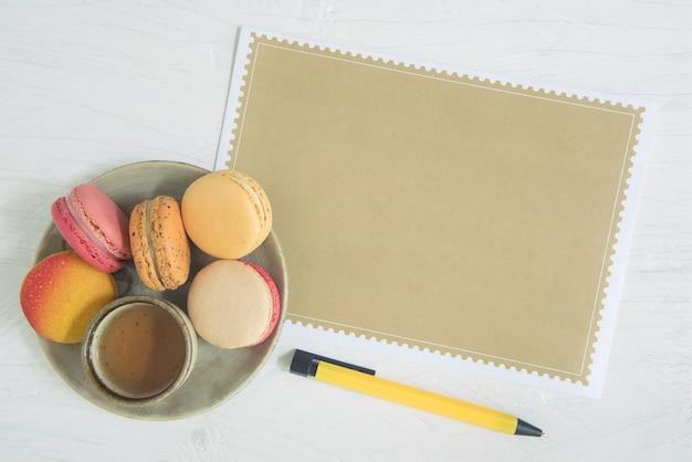Page vide de papier brun et macaron dessert sucré sur fond blanc. Photo Premium