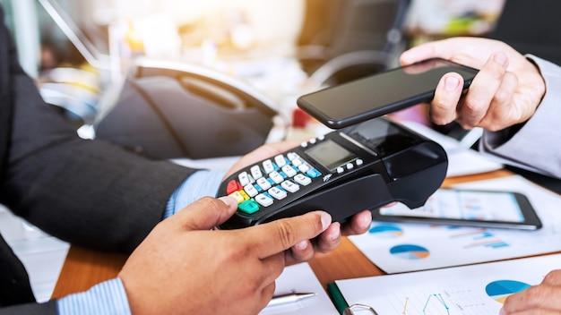 Paiement de l'homme d'affaires par la technologie nfc avec un lecteur de carte de crédit et une application pour smartphone. Photo Premium