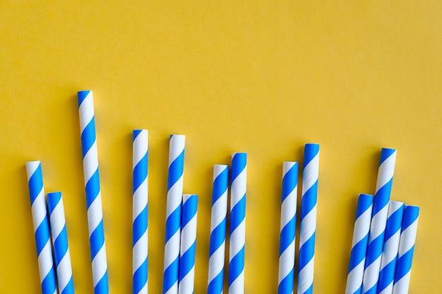 Des pailles à rayures pour boire du jus ou des cocktails sont sur fond jaune. Photo Premium