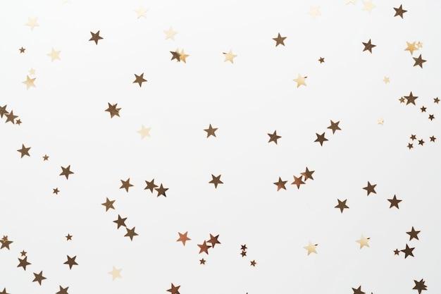 Paillettes d'or, étoiles de confettis isolés sur blanc. fond de noël, fête ou birthdau. Photo Premium