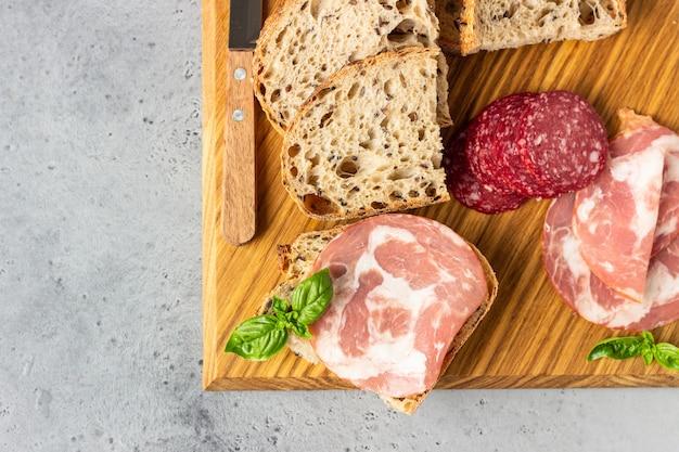 Pain artisanal traditionnel aux graines et saucisse de porc et salami servi sur une planche à découper en bois. sandwich ouvert avec saucisse de porc. Photo Premium