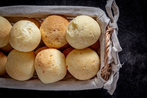 Pain au fromage brésilien fait maison, aka 'pao de queijo' dans un panier rustique. Photo Premium