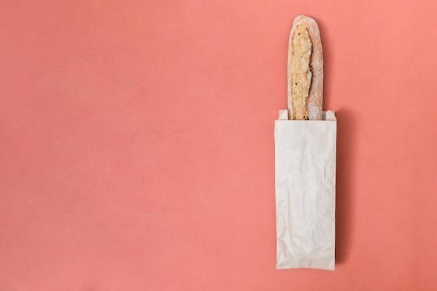 Pain baguette dans le sac en papier sur le fond coloré Photo gratuit