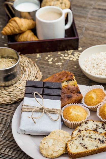 Pain, biscuits, cupcake et chocolat noir sur la plaque Photo gratuit